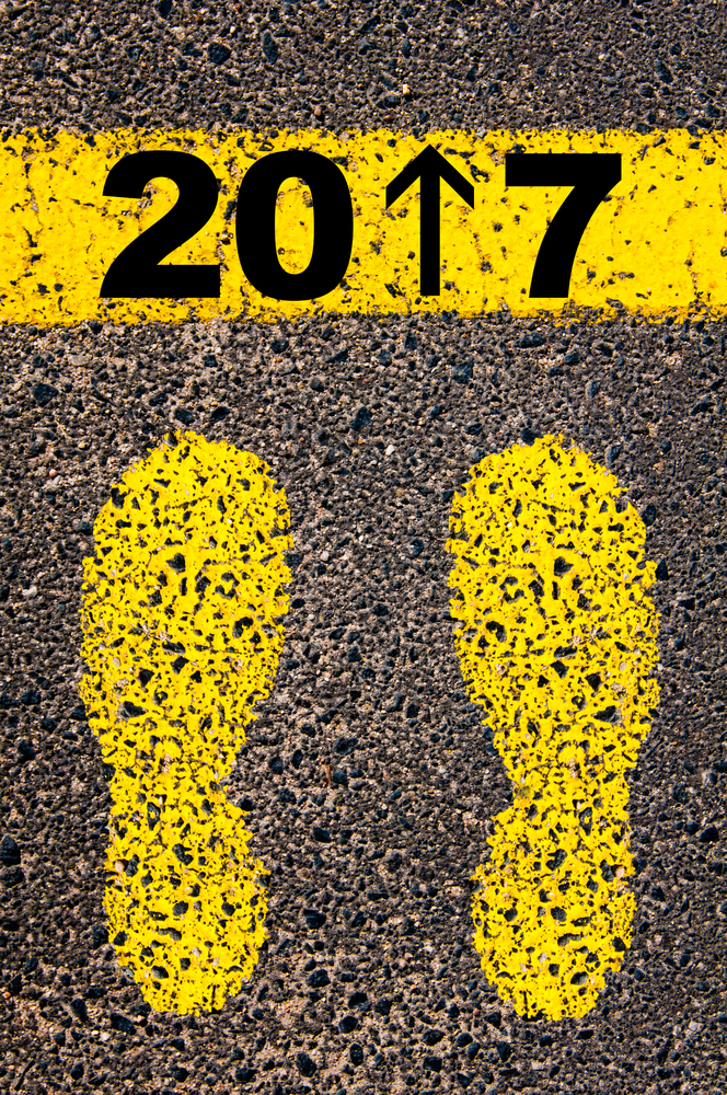Year 2017 is coming message, number 1 replaced with arrow pointing forward. Conceptual image with yellow paint footsteps on the road in front of horizontal line over asphalt stone background.